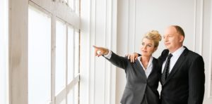 Zwei Personen schauen aus einem Fenster.